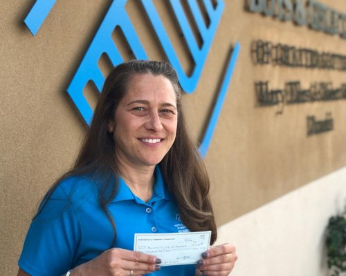 woman in blue shirt holding a check